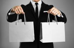 Uomo d'affari in un vestito nero che tiene una borsa di carta grigia del regalo Fine in su Fondo isolato immagini stock