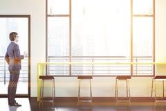 Uomo d'affari in una barra del sottotetto interna, tavola gialla Fotografie Stock
