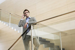 Uomo d'affari Using Cellphone While che sta contro l'inferriata di vetro immagine stock libera da diritti