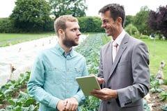 Uomo d'affari Using Digital Tablet nel corso della riunione con l'agricoltore In F Fotografia Stock