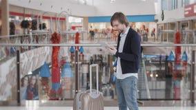Uomo d'affari Using Digital Tablet nel salotto di partenza dell'aeroporto Giovani free lance con la valigia di laggage nella zona archivi video