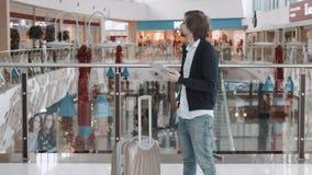 Uomo d'affari Using Digital Tablet nel salotto di partenza dell'aeroporto Giovani free lance con la valigia di laggage nella zona stock footage