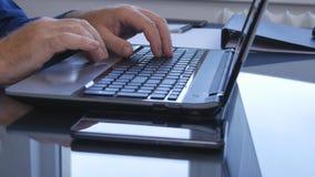 Uomo d'affari Using Laptop in ufficio che introduce informazioni elettroniche fotografie stock