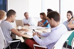 Uomo d'affari Using Mobile Phone nella riunione della sala del consiglio Immagini Stock Libere da Diritti