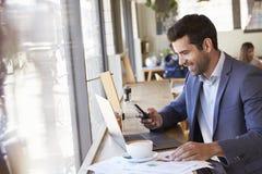 Uomo d'affari Using Phone Whilst che lavora nella caffetteria fotografie stock