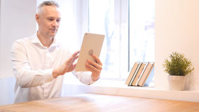 Uomo d'affari Using Tablet di medio evo sul lavoro Immagine Stock Libera da Diritti
