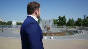 Uomo d'affari in vestito blu che sta sulla via davanti alla fontana Movimento lento stock footage