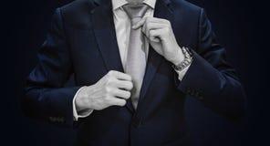 Uomo d'affari in vestito blu scuro che lega cravatta grigia su fondo blu Immagini Stock Libere da Diritti
