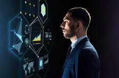 Uomo d'affari in vestito che esamina proiezione virtuale Immagini Stock