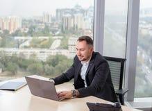Uomo d'affari in vestito che lavora al computer portatile Immagini Stock