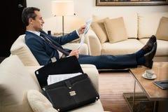 Uomo d'affari in vestito convenzionale che si siede nella poltrona e nella lettura Fotografia Stock