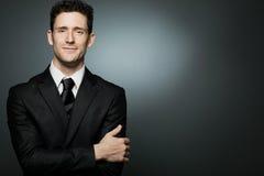 Uomo d'affari in vestito nero che esprime positività. Immagine Stock