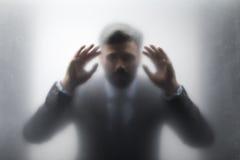 Uomo d'affari in vestito nero che guarda attraverso il vetro Fotografia Stock