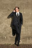 Uomo d'affari in vestito nero che parla sul telefono cellulare all'aperto Immagine Stock