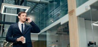 Uomo d'affari in vestito nero che parla sul telefono e sul caffè asportabile bevente Immagine Stock