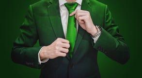 Uomo d'affari in vestito verde che lega cravatta verde Ambiente, agricoltura ed affare verde Fotografia Stock Libera da Diritti