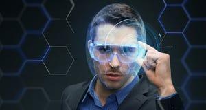 Uomo d'affari in vetri 3d con l'ologramma virtuale fotografie stock