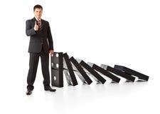 Uomo d'affari vicino ad una pila di domino Immagini Stock Libere da Diritti