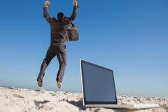 Uomo d'affari vittorioso che salta lasciando il suo computer portatile Fotografia Stock Libera da Diritti