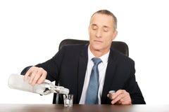 Uomo d'affari in vodka di versamento dell'ufficio in un vetro Fotografie Stock