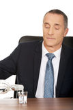 Uomo d'affari in vodka di versamento dell'ufficio in un vetro Fotografia Stock