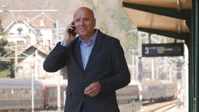 Uomo d'affari Waiting e parlare con telefono cellulare in una stazione ferroviaria fotografie stock libere da diritti