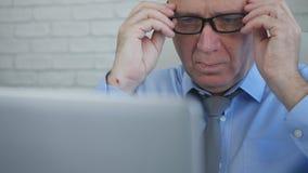 Uomo d'affari Wearing Eyeglasses Read preoccupato da informazioni finanziarie del computer portatile immagine stock libera da diritti