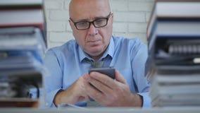 Uomo d'affari Wearing Eyeglasses Text facendo uso del cellulare in ufficio immagine stock libera da diritti