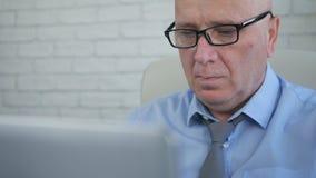 Uomo d'affari Wearing Eyeglasses Working facendo uso di un computer portatile nella stanza dell'ufficio fotografia stock