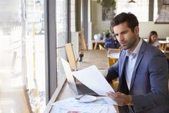 Uomo d'affari By Window Working sul computer portatile in caffetteria fotografie stock libere da diritti
