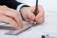 Uomo d'affari Working On Blueprint allo scrittorio Fotografie Stock