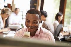 Uomo d'affari Working At Desk che per mezzo del telefono cellulare Immagine Stock Libera da Diritti