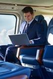 Uomo d'affari Working On Laptop nella cabina dell'elicottero durante il volo Fotografie Stock