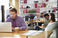 Uomo d'affari Working On Laptop in ufficio occupato fotografie stock libere da diritti