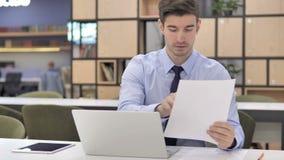 Uomo d'affari Working sui documenti di affari in ufficio archivi video