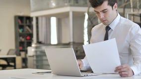 Uomo d'affari Working sui documenti e sul computer portatile, lavoro di ufficio video d archivio