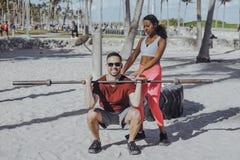 Uomo d'aiuto della donna con l'allenamento sulla spiaggia Fotografie Stock