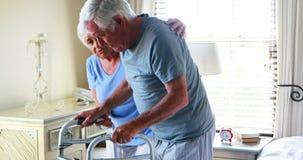 Uomo d'aiuto della donna senior da camminare con il camminatore video d archivio