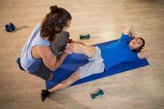 Uomo d'aiuto di forma fisica dell'istruttore di yoga con le flessioni della gamba Fotografia Stock
