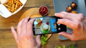 Uomo d'avanguardia facendo uso del suo smartphone che prende la grande fotografia saporita fresca del pranzo dell'hamburger per l video d archivio