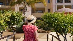 Uomo d'invito della giovane donna felice per seguirlo con la sua mano che porta vestito, gli occhiali da sole e cappello rossi Po video d archivio
