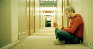 Uomo dai capelli grigio in abbigliamento casual facendo uso del suo smartphone nel corridoio dell'hotel archivi video