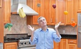 Uomo dai capelli grigio attraente che pensa alla dieta Immagine Stock