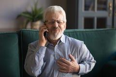 Uomo dai capelli grigio che tocca petto, avendo attacco di cuore, chiamante emergenza immagine stock