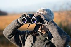 Uomo dai capelli grigio con binoculare Fotografia Stock