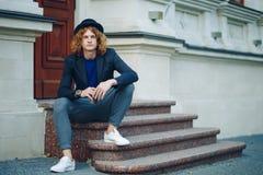 Uomo dai capelli rossi dei pantaloni a vita bassa che si siede sul pensiero delle scale Fotografie Stock Libere da Diritti