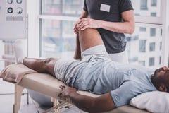 Uomo dalla carnagione scura rilassato che visita il suo massaggio di riabilitazione immagini stock