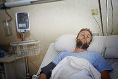Uomo danneggiato che si trova a letto stanza di ospedale che riposa dal dolore che guarda nel cattivo stato di salute Immagini Stock Libere da Diritti