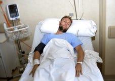 Uomo danneggiato che si trova a letto stanza di ospedale che riposa dal dolore che guarda nel cattivo stato di salute Fotografie Stock Libere da Diritti