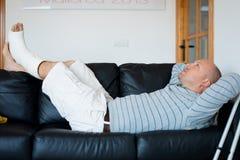 Uomo danneggiato che si trova sul sofà Immagine Stock